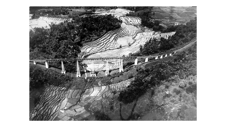 Pandangan udara dari sebuah jembatan kereta api di lanskap sawah di Jawa Barat