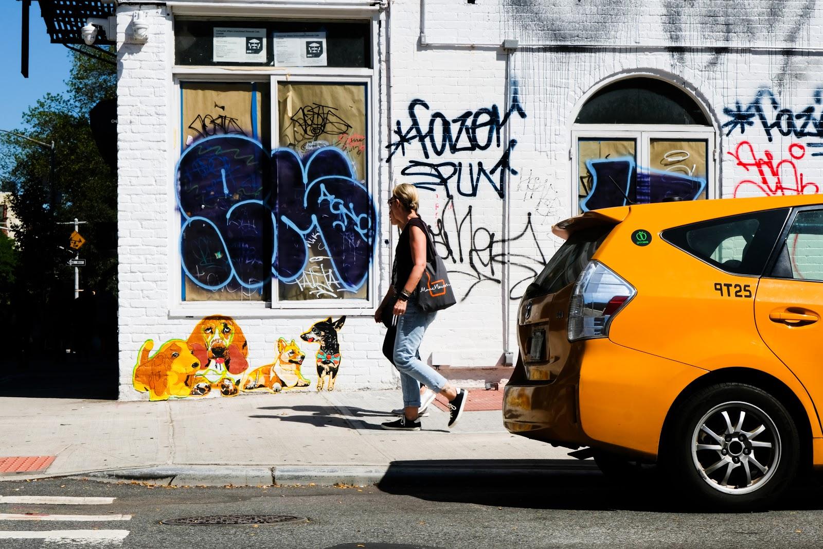 Person walking next to graffiti