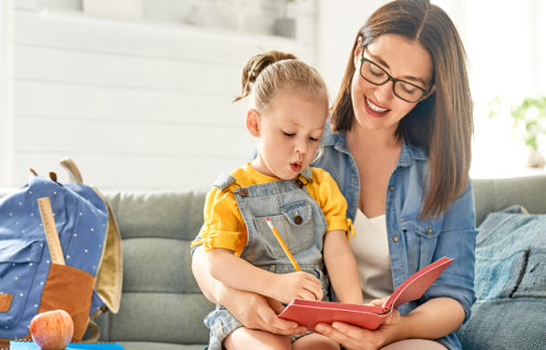 mother and her daughter are writing in notebook.