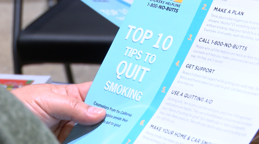 Event goer holds info on how to quit smoking