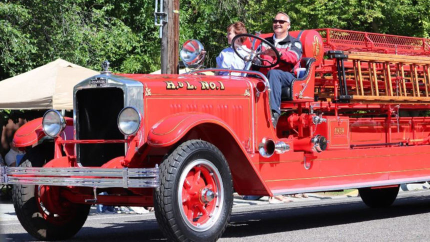 IFFD Deputy Fire Chief Dave Coffey and wife, Michele Coffey, behind the wheel of the old ladder truck during the Independence Day parade (2019).