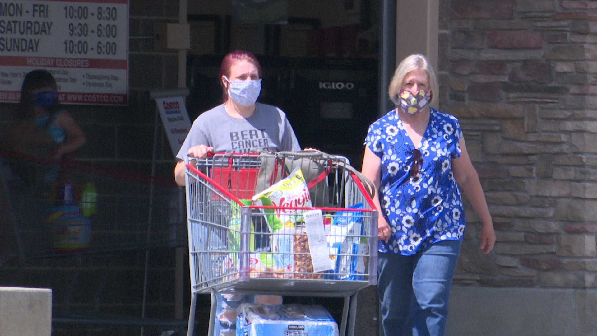 two women wearing masks as they leave costco